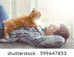 Stock photo young man with cute cat lying on floor near window 599647853