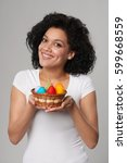 Smiling mixed race Caucasian - African American female showing a small basket with colorful Easter eggs