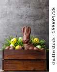 Small photo of Traditional delicious Easter chocolate bunny and eggs inside a wooden crate