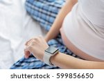 pregnant woman checking time on ... | Shutterstock . vector #599856650