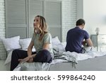 sad couple sitting on bed | Shutterstock . vector #599864240