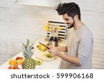 young man cutting fruit in the... | Shutterstock . vector #599906168