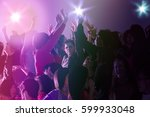 crowd dancing with arms raised | Shutterstock . vector #599933048