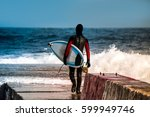 surfer goes into water wearing... | Shutterstock . vector #599949746