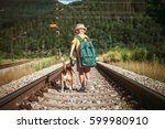 Stock photo little boy with backpack walks with beagle dog on the emty railway in forest 599980910