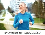 young blonde woman is jogging... | Shutterstock . vector #600226160