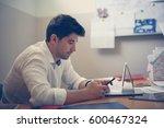 cheerful business man typing a... | Shutterstock . vector #600467324