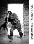 Small photo of Black & white photo of terrorist attack with automatic assault rifle in ruined building.Portrait of armed military man in heavy combat ammunition targeting with machine gun in ruins.Airsoft training
