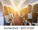 Small photo of passenger seat, Interior of airplane with passengers sitting on seats and stewardess walking the aisle in background. Travel concept,vintage color