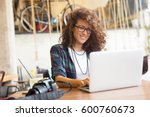 Attractive businesswoman using laptop at city cafe. Toothy smile. - stock photo