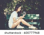 Small photo of Outdoor portrait of pretty woman playing game on mobile phone and holding a cup of coffee in the park. life style, vintage style.