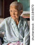 Small photo of Absent-minded elderly asian women portrait. She is a Thai person.
