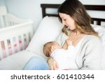 a young mother holding her baby ... | Shutterstock . vector #601410344