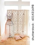 Small photo of layman figure with lace on it standing at the folding screen and pillows