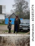 Small photo of RIVNE, UKRAINE - 04 November 2008: A man of low stature and a woman standing near the car on the streets of the village