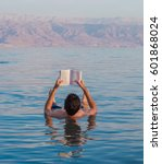 young man reads a book floating ... | Shutterstock . vector #601868024