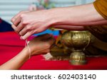 Small photo of close up Monk bind to holy thread for hand woman