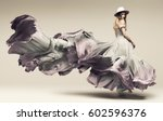 Stock photo woman dancing in fluttering purple dress and hat in studio 602596376