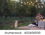 apple orchard couple sitting on ... | Shutterstock . vector #602600030