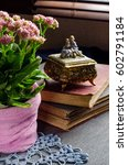 Small photo of Flowering Kalanchoe. Pink flowers. Flowering Kalanchoe. Pink flowers. Doily crochet. Old books, vintage jewelry box figurines. Vintage style. Place for text. Selective focus.