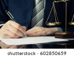 Stock photo lawyer working with agreement in office man signing hand writing pen attorney concept 602850659