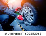 Small photo of Car mechanic installing sensor during suspension adjustment. Wheel alignment work at repair service station