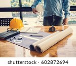 blueprint on wooden desk with... | Shutterstock . vector #602872694