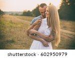 loving couple in a field | Shutterstock . vector #602950979
