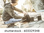young skater playing music from ... | Shutterstock . vector #603329348