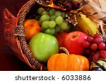 Thanksgiving cornucopia filled with autumn fruits and vegetables. Shallow DOF with focus on basket edge. - stock photo
