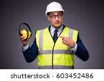 Man wearing hard hat and construction vest - stock photo