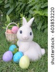 Small photo of Easter bunny and Easter eggs, rabbit statues and colorful pastel eggs at the backyard garden. Soft focus on the eyes of Easter bunny. Easter eggs hunting activity concept.