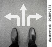 Small photo of Businessman in black leather shoes standing at the crossroad making decision which way to go - three ways to choose.