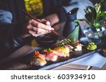 man eating sushi set with... | Shutterstock . vector #603934910
