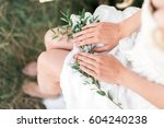 Stock photo smiling beautiful bride wearing a natural flower wreath and standing in the golden summer fields 604240238