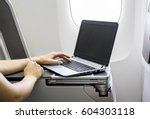 woman using laptop in airplane  | Shutterstock . vector #604303118