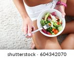 fit woman eating healthy salad... | Shutterstock . vector #604342070