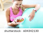 fit woman eating healthy salad... | Shutterstock . vector #604342130