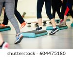 Small photo of Women doing aerobic class with steppers to people group on fitness center detail of raised feet during aerobic step exercise at gym aerobics and people concept people working out with steppers in gym.