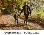father and son on autumn walk... | Shutterstock . vector #604632263