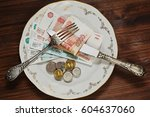 Small photo of Different rubles notes and coins on the plate with golden ornamentation and vintage silver fork and knife