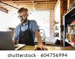 a man in a bicycle repair shop... | Shutterstock . vector #604756994