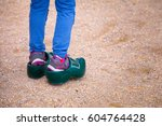 Small photo of Little girl trying to wear a typical Dutch clog
