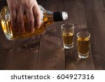 pouring alcohol in shot glass... | Shutterstock . vector #604927316