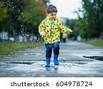 Little Boy In Raincoat And...