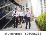 Stock photo full length of smiling businesspeople discussing about a meeting while walking in the city 605006288