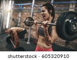 fit couple lifting barbells in... | Shutterstock . vector #605320910