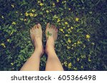 feet in grass on meadow with... | Shutterstock . vector #605366498