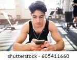 hispanic man in gym resting ... | Shutterstock . vector #605411660