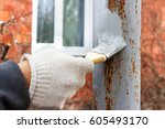 gloved hand painting primer... | Shutterstock . vector #605493170